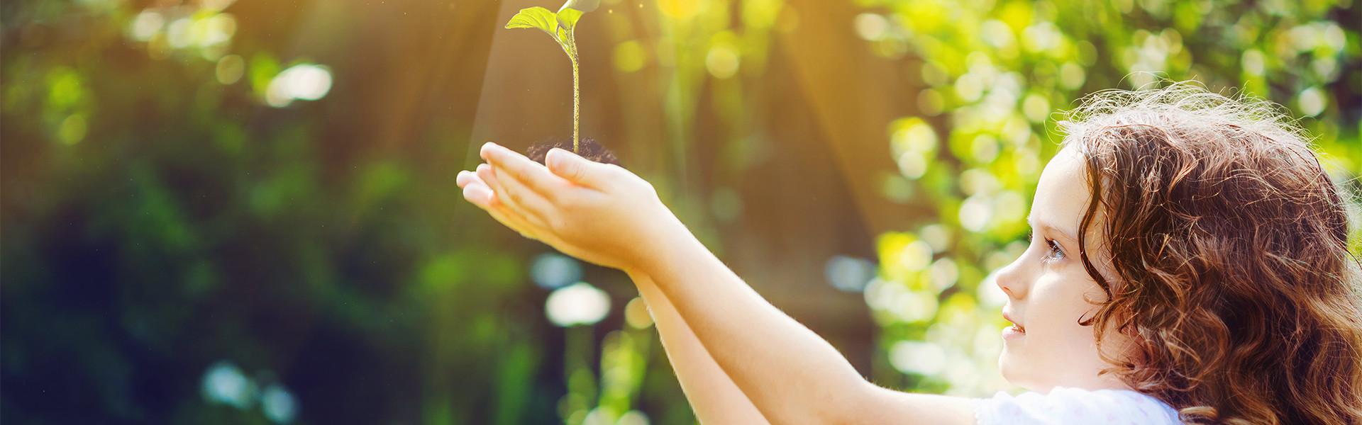 ילדה מחזיקה צמח בחברת תרגום יוניברסל